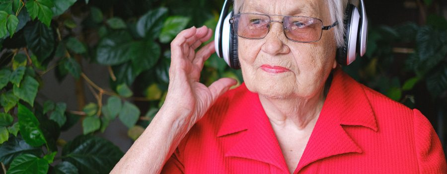 An elderly woman using headphones