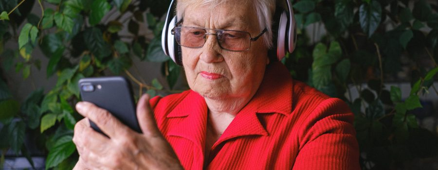 Elderly woman wearing headphones and using a cell phone