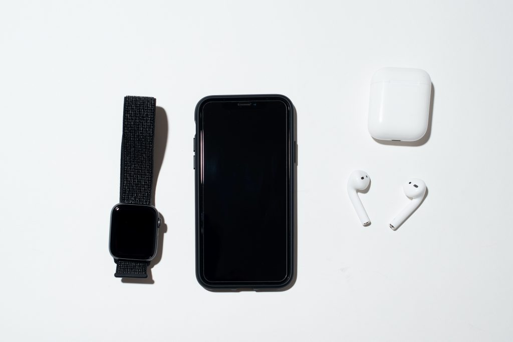A photo of a phone, headphones, and a watch.